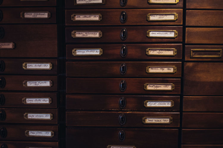 Indoors  In A Row Repetition No People Order Drawer Wood - Material Full Frame Stack Backgrounds Safety Close-up Arrangement Organization Side By Side Brown Locker Old Text Security Cabinet