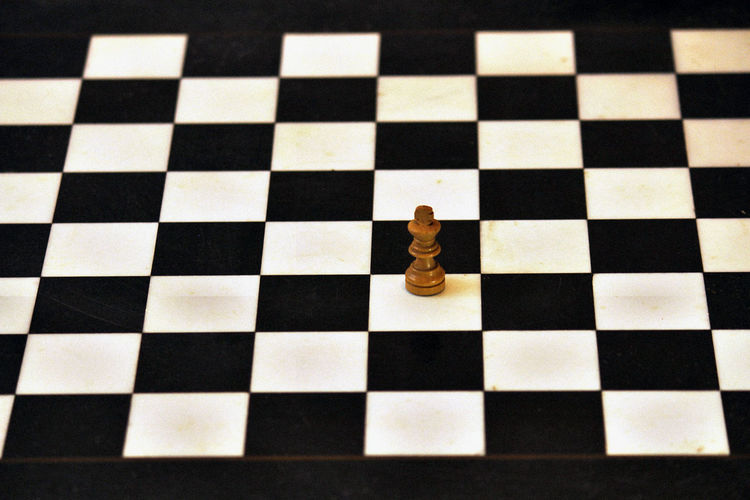 High angle view of chess piece on checked board