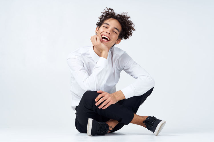 Young man sitting against white background