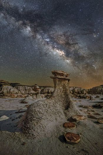 View of rocks on land against sky at night