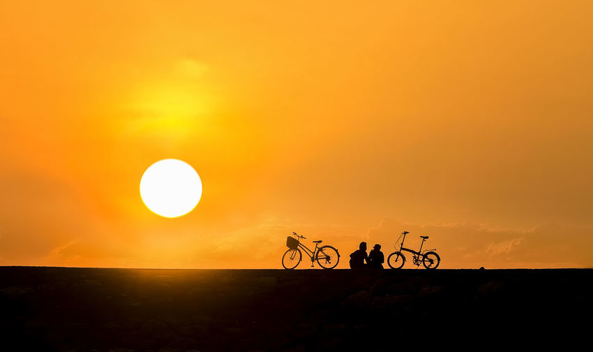Young couple in love chasing each others on a bicycle during sunrise near Karang Beach Sanur Bali Indonesia. soft tones and warm Bali Dating Holiday INDONESIA Love Sanur Beauty In Nature Bicycle Day Land Vehicle Landscape Mode Of Transport Motorcycle Nature Outdoors Real People Scenics Silhouette Silhouette People Sky Sun Sunrise Sunset Transportation Vacation