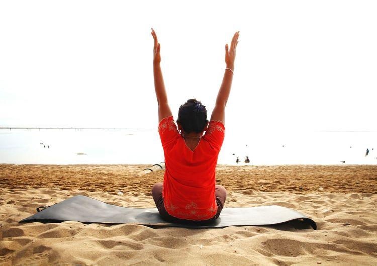 Rear view of woman practicing yoga at beach against clear sky