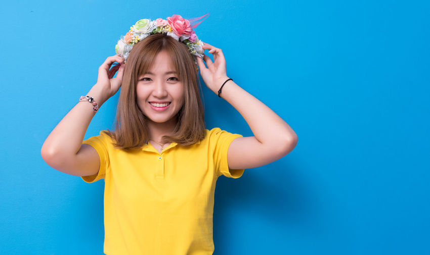 Portrait of beautiful woman wearing flowers against blue background