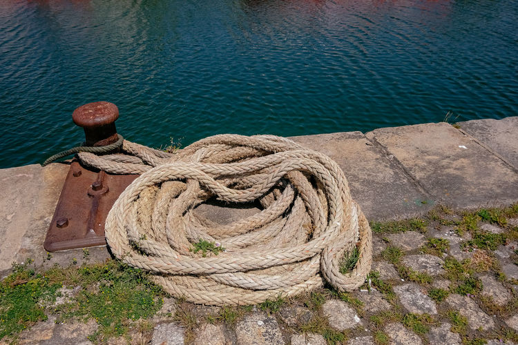 High angle view of rope tied on wooden post