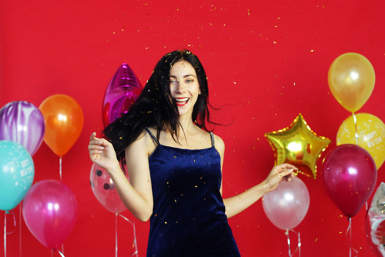 Portrait of smiling young woman with red balloons