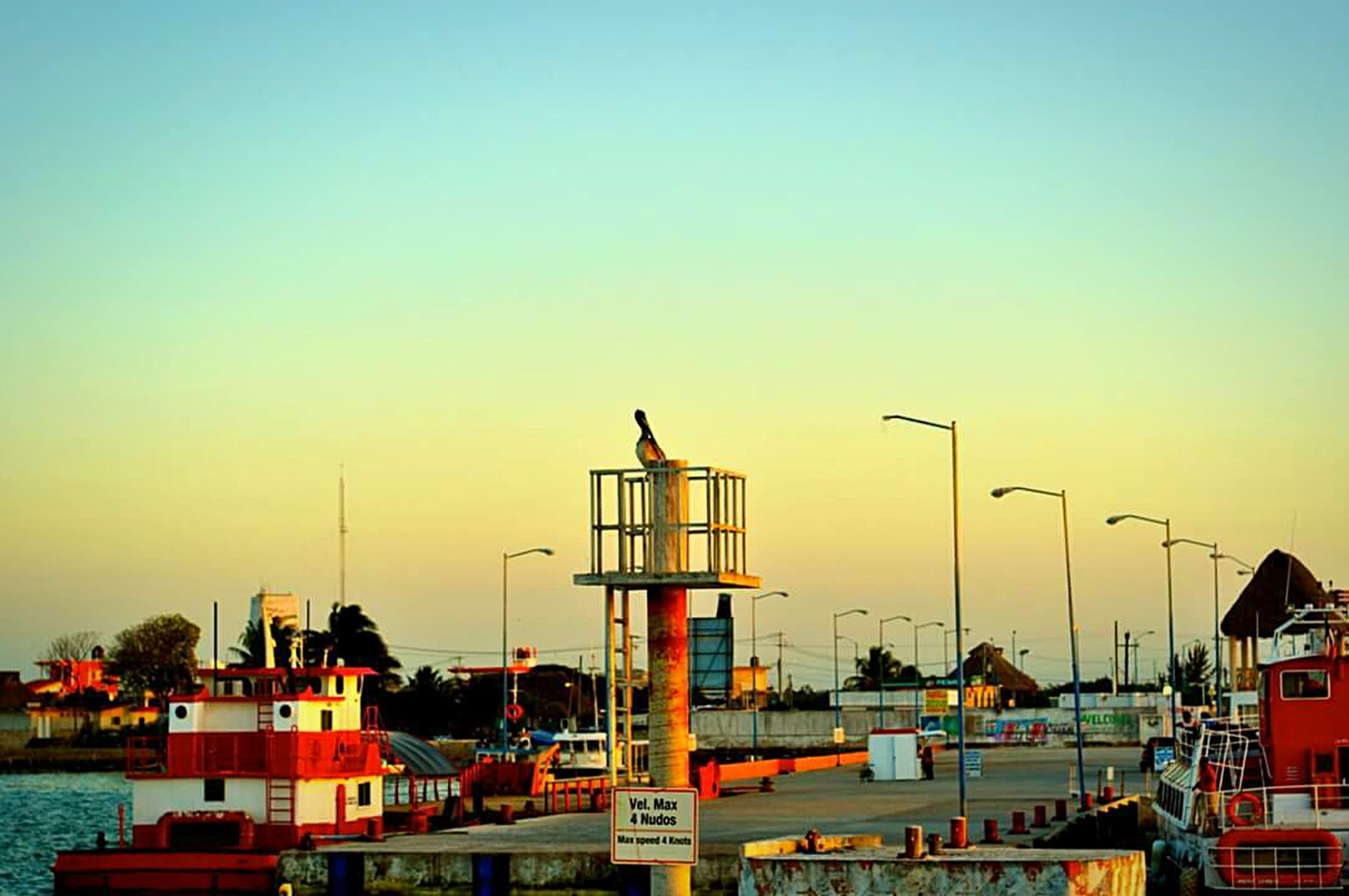 building exterior, architecture, built structure, clear sky, copy space, sunset, orange color, blue, industry, outdoors, no people, city, house, residential structure, harbor, residential building, water, sky, building, roof
