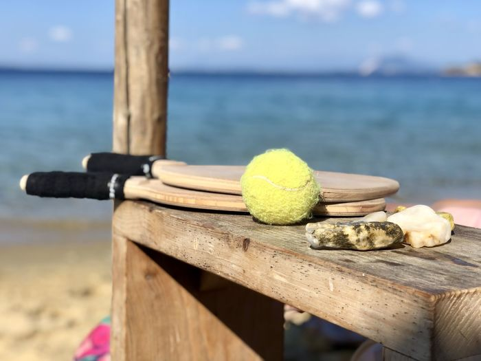 Close-up of balls on wooden table by sea