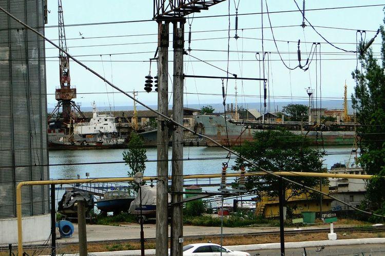 Electricity pylon by city against sky