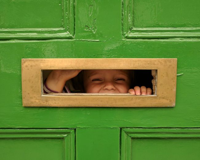 Close-Up Of Boy Looking Through Hole