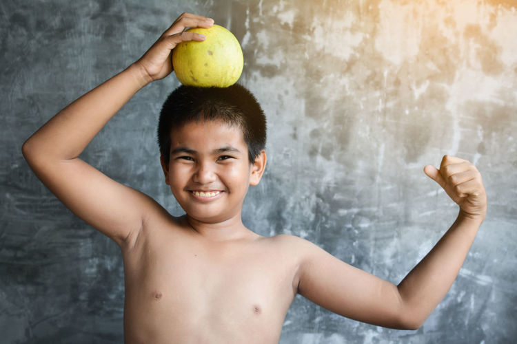 Portrait of smiling shirtless boy holding fruit while standing against wall