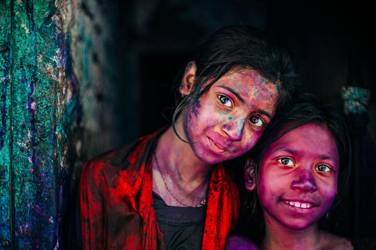 Portrait of smiling sisters with powder paints