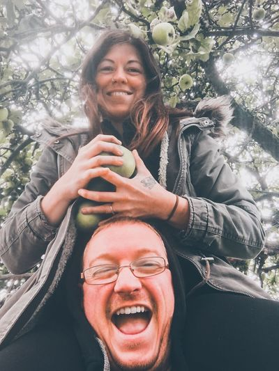 Portrait of smiling woman holding fruits over man against tree