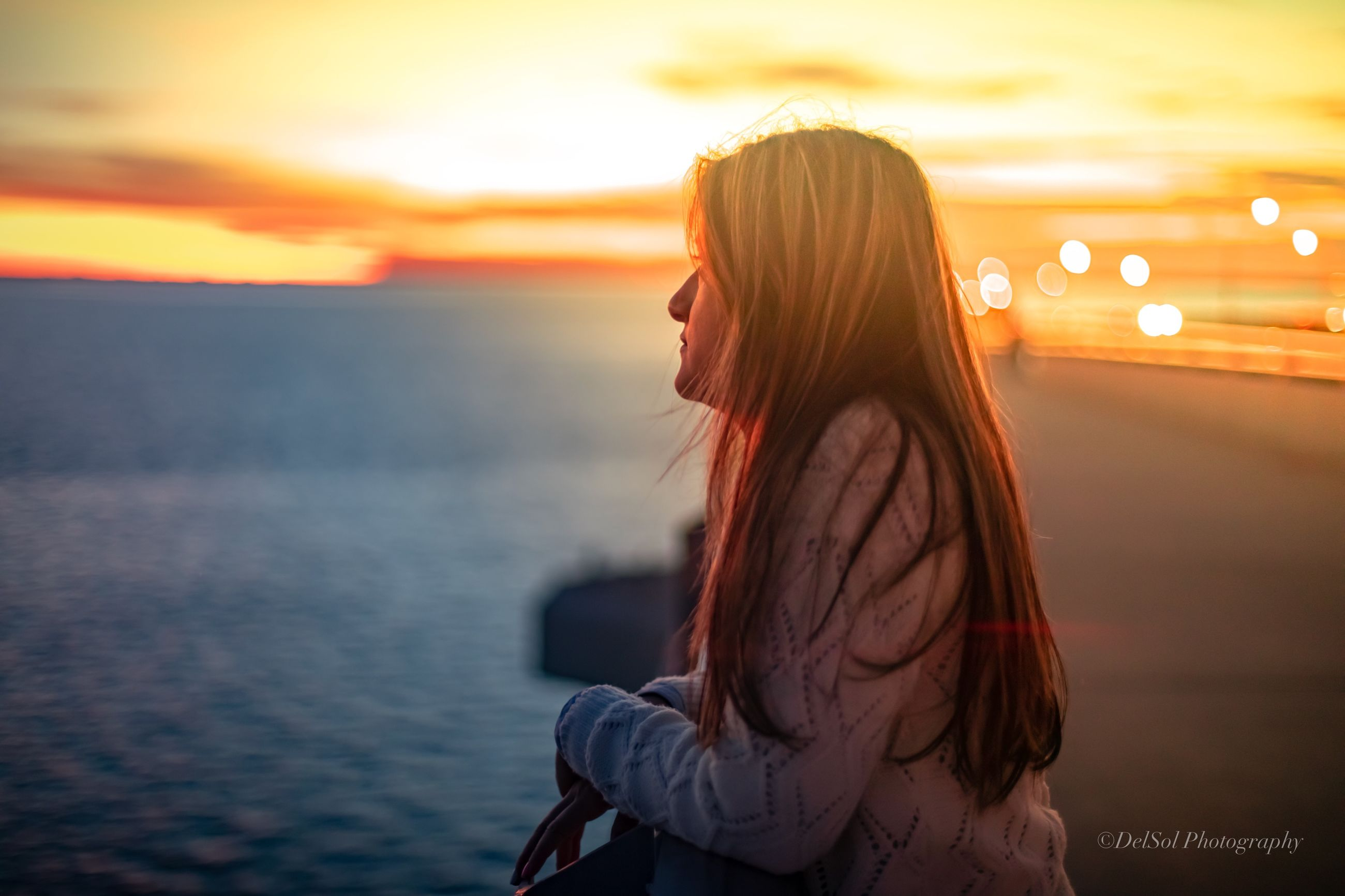 sunset, real people, sky, one person, water, lifestyles, women, orange color, leisure activity, side view, focus on foreground, beauty in nature, sea, long hair, adult, hairstyle, young women, young adult, hair, outdoors