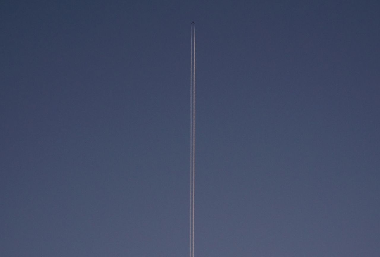 LOW ANGLE VIEW OF VAPOR TRAILS AGAINST BLUE SKY