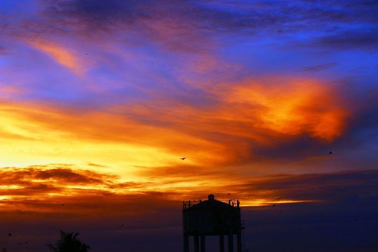 Silhouette water tower during orange sunset
