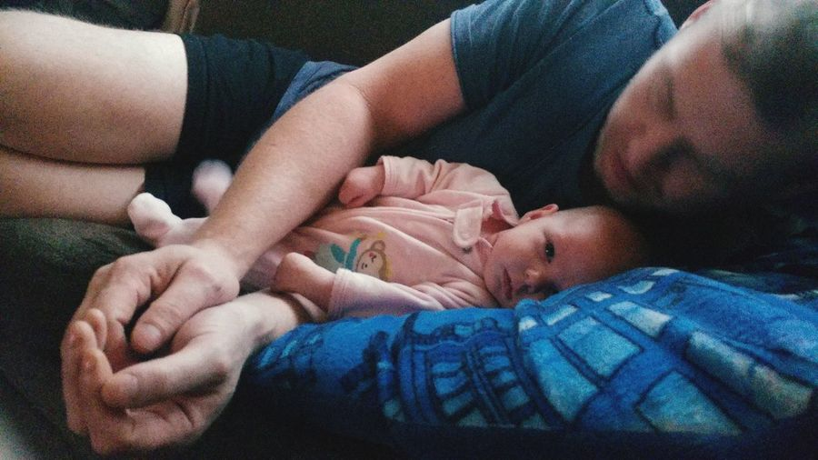 Midsection of father with baby sleeping