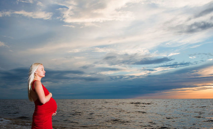 Pregnant woman standing in front of baltic sea against cloudy sky