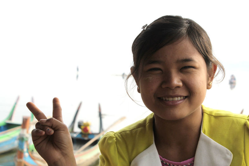 U-BEIN BRIDGE/AMARAPURA, MYANMAR JAN 22, 2016: Portrait of a burmese girl on a school trip to U-Bein Bridge is being exited to have her photo taken by a foreigner. These schoolgirls and their class mates were patiently waiting in the bus for their teacher to come back when I approached them and asked (with hand and feet) wether I could take a photo. Obviously they agreed and were quite excited about it, too. It took me one or two minutes in total to finish but another 15 minutes for the girls to take photos with their smartphones of each of them with me. Since I only own a 18-55mm lens I always have to get really close to take portraits, hence, I always have to ask beforhand if solely out of respect. But it is always a nice opportunity to chat or at least to exchange smiles, too. Amarapura Childhood Culture Day Excursion Face Girl Happiness Happy Headshot Looking At Camera Mandalay Myanmar One Person Outdoors People Portrait Real People School Smiling Tradition Travel U-bein Bridge,Myanmar Victory Young