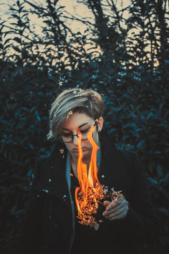 Front View One Person Leisure Activity Burning Real People Forest Flame Fire - Natural Phenomenon Nature Land Tree Fire Lifestyles Blond Hair Heat - Temperature Young Adult Waist Up Focus On Foreground Outdoors Hair Hairstyle Teenager Contemplation Bonfire