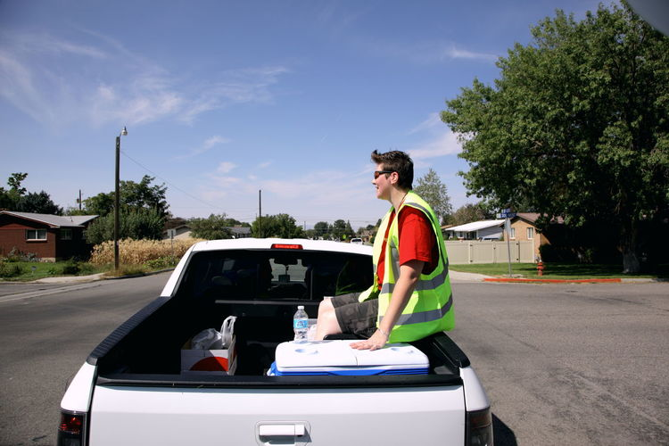 Side View Of Female Worker Sitting On Pick-Up Truck Against Sky