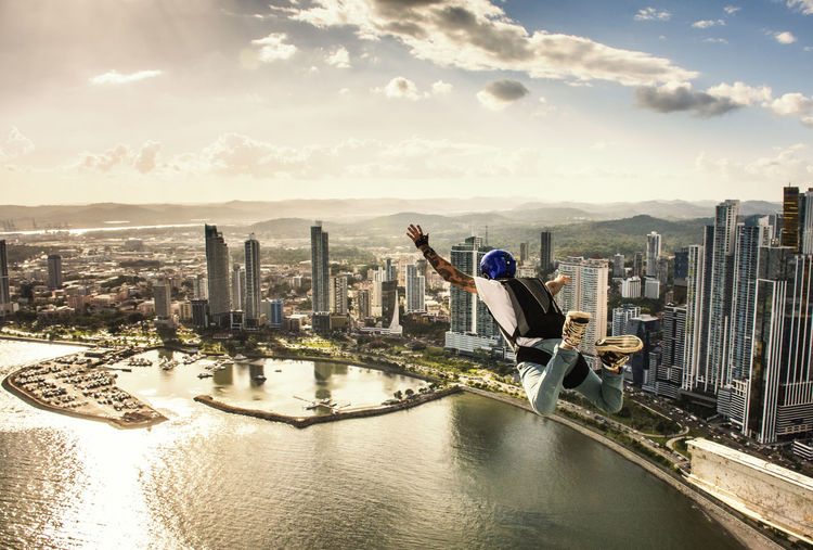 Full length of man jumping in city over sea at sunset