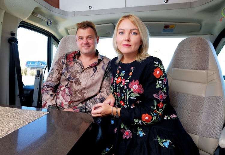 Portrait of smiling couple sitting in motor home