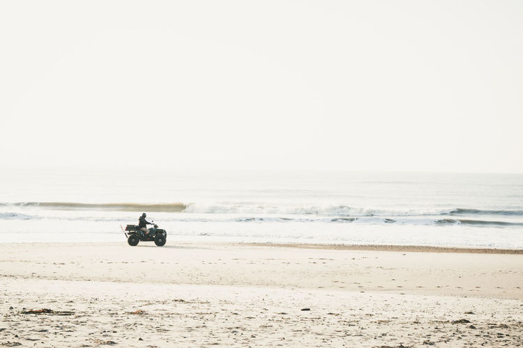 Man riding motorcycle at beach against sky