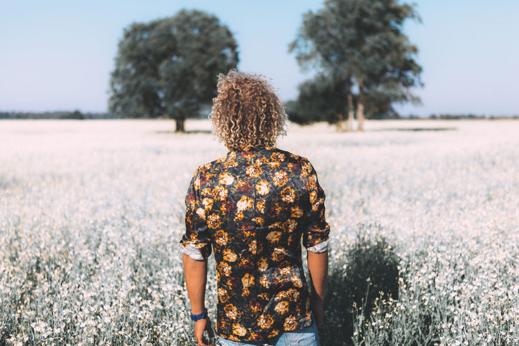 Rear view of man standing amidst flowering plants