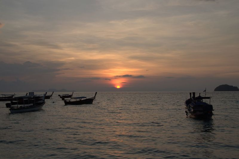 Longtail boats moving on sea against sky during sunset