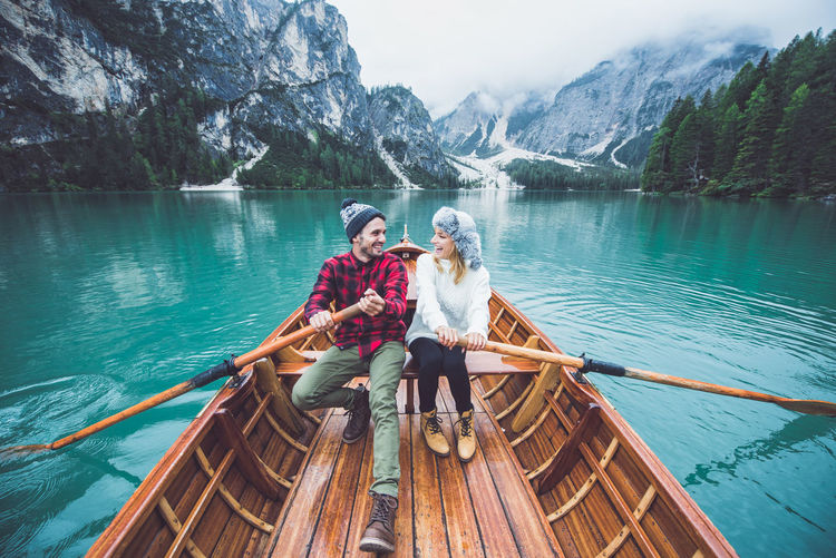 People sitting on boat in lake against mountain