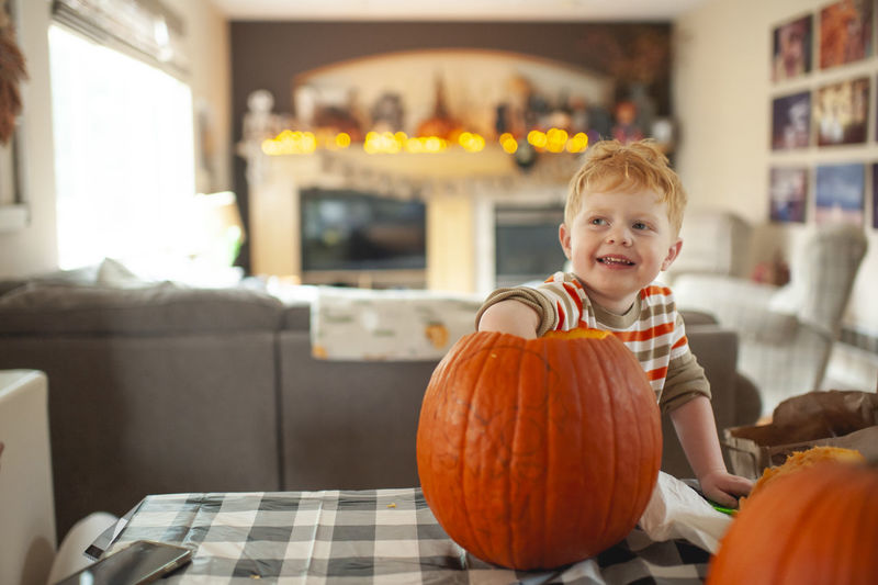 Portrait of smiling boy with pumpkins in kitchen