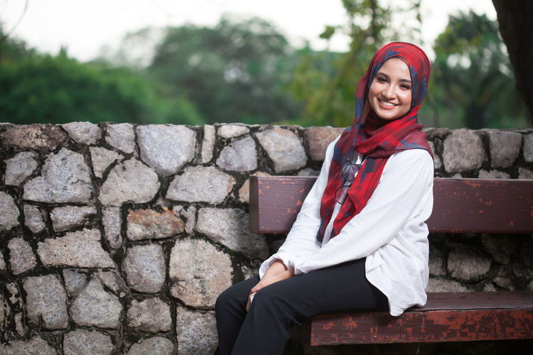 Portrait Of Smiling Young Woman Wearing Hijab While Sitting On Bench