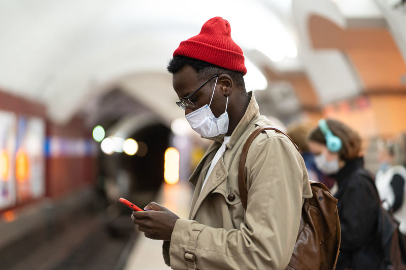 Man wearing mask using smart phone at subway station
