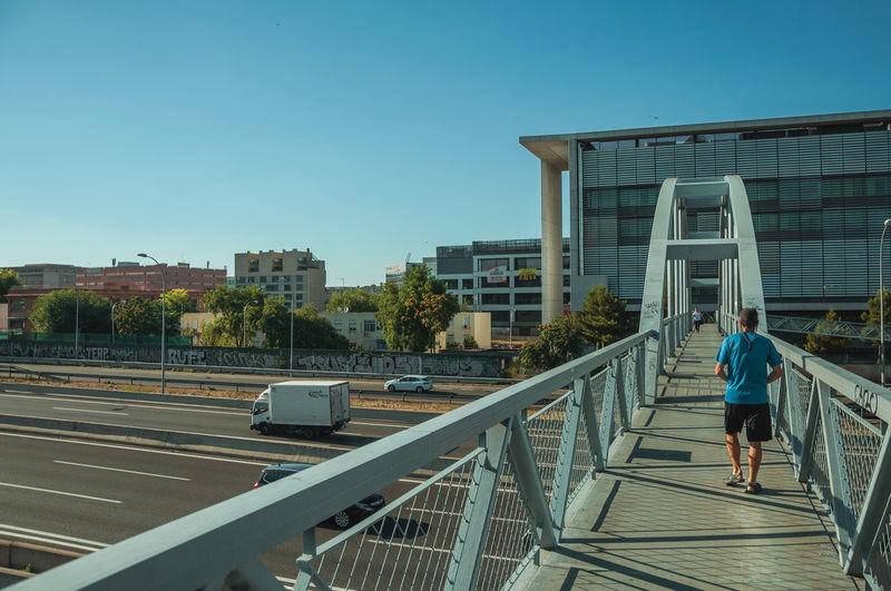 Rear view of woman walking on bridge in city