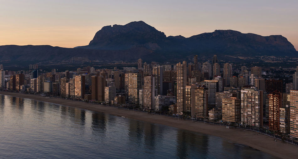 Aerial view of a Benidorm city coastline at sunset. Benidorm is a modern resort city, one of the most popular travel destinations in Spain. Costa Blanca, Alicante province Aerial View Alicante Beach Benidorm Spain City Cityscape Coastline Costa Blanca Highrise Buildings Idyllic Landmark Landscape Mediterranean Sea Mountains Nature Office Building Picturesque Reflection Skycrapers SPAIN Sundown Sunset Tourist Resort Travel Destinations Waterside