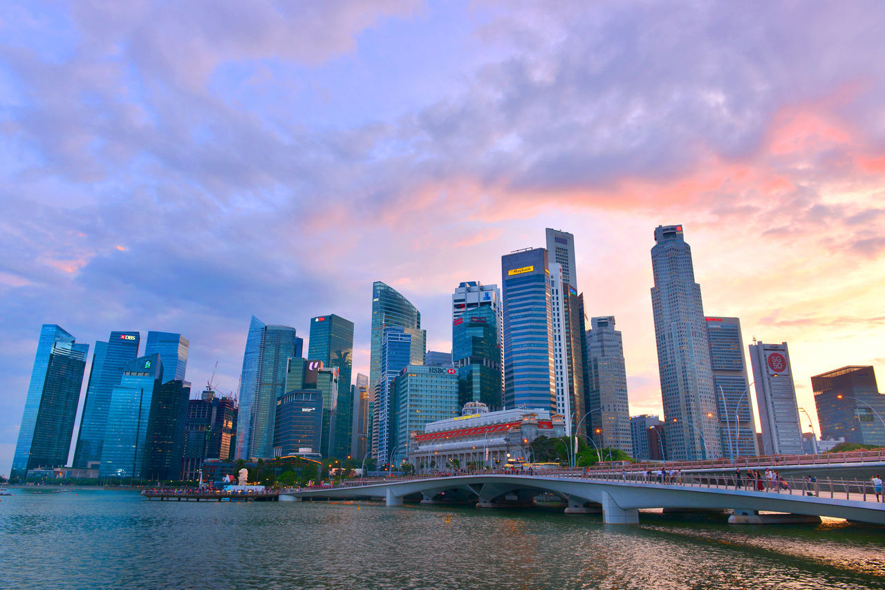 architecture, skyscraper, city, built structure, modern, building exterior, sky, urban skyline, cityscape, tower, connection, skyline, downtown district, no people, development, river, outdoors, travel destinations, growth, bridge - man made structure, cloud - sky, waterfront, sunset, tall, water, day
