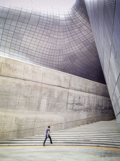 Man walking on steps at dongdaemun design plaza in city