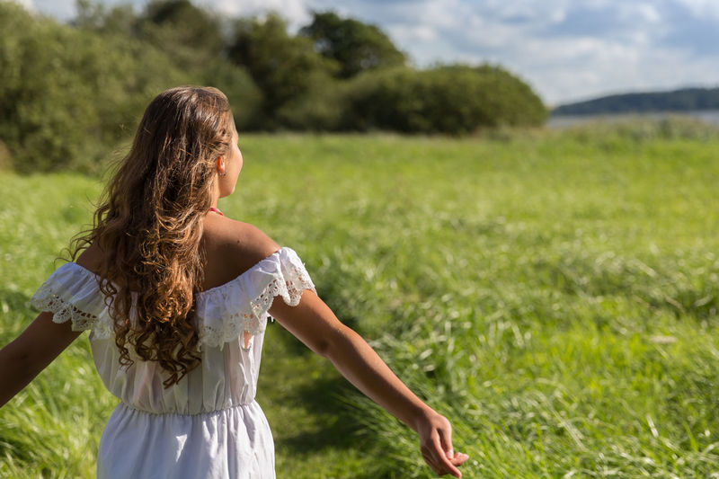 Adult Beautiful Woman Casual Clothing Day Enjoyment Of Life Enjoyments Fashion Field Focus On Foreground Grass Hair Hairstyle Land Leisure Activity Lifestyles Long Hair Nature One Person Outdoors Plant Real People Rear View Standing Women Young Women