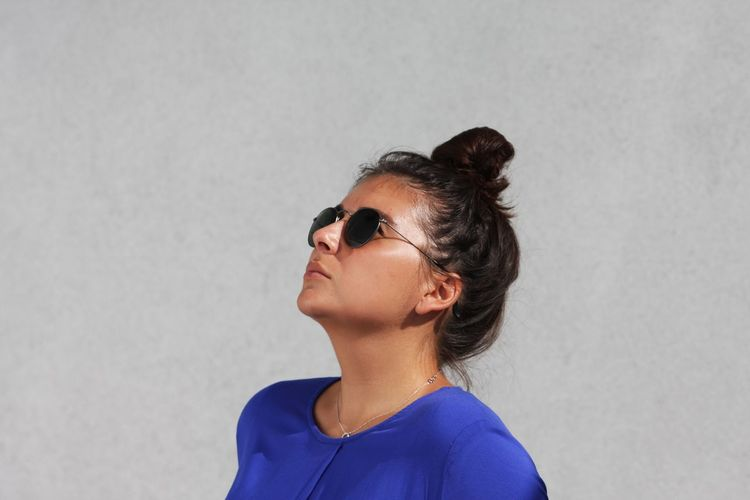 Streetphotography Street Fashion Street Style Street Style from Around The World Grey Grey Color Blue Blue Dress Rayban EyeEm Selects Headshot One Person Portrait Adult Studio Shot Glasses Hair Young Adult Women Looking Gray Background Hairstyle Human Body Part Indoors  Profile View Copy Space Body Part Fashion Hair Bun Contemplation