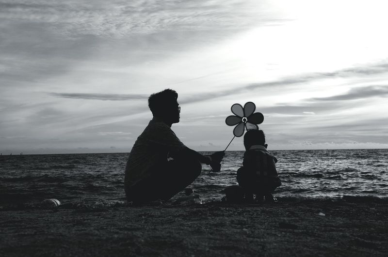 Father and son with pinwheel crouching on sea shore against sky