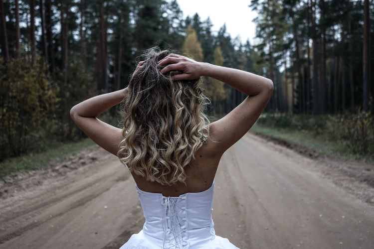 Rear view of young woman with hand in hair standing on road at forest