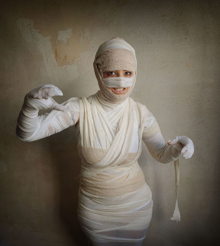 Portrait Of Woman Wrapped With Bandages Against Wall During Halloween