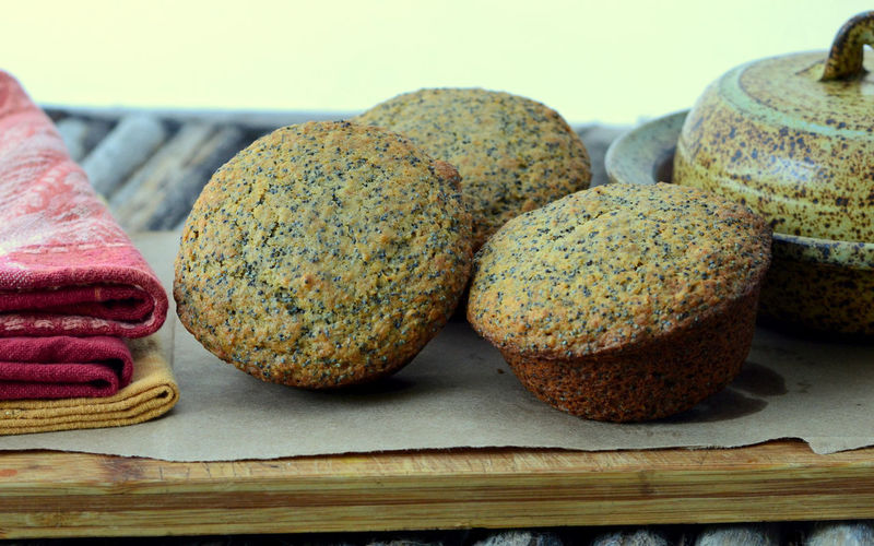 Close up of Three Poppy Seed Muffins; served on a wooden board with napkins and butter dish. Breakfast Homemade Napkins Profile Baked Bread Breakfast Muffins Brown Butter Dish Close Up Close-up Closeup Food Food And Drink Health Food Healthy Eating Muffins Parchment Paper Poppy Seed Muffins Poppy Seeds Ready-to-eat Tasty Three Wooden Board
