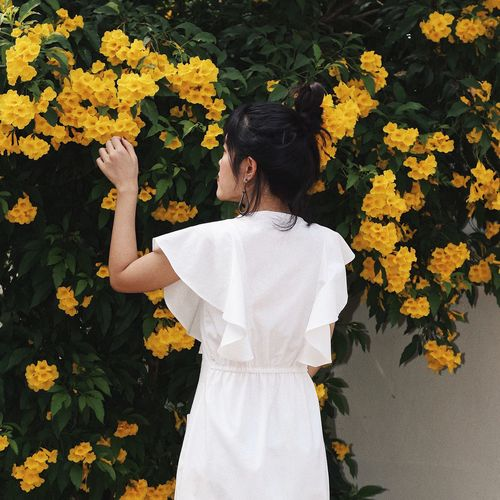 Rear view of woman standing by yellow flowering plants