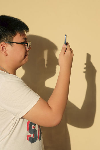 Side view of teen kid using mobile device with his shadow in the background. Tech Visual Creativity Boy Casual Clothing Device Eyeglasses  Holding Kid Leisure Activity Lifestyles Mobile One Person People Photography Selfie Shadow Side View Smartphone Sunlight Technology Teen Teenager Using Waist Up
