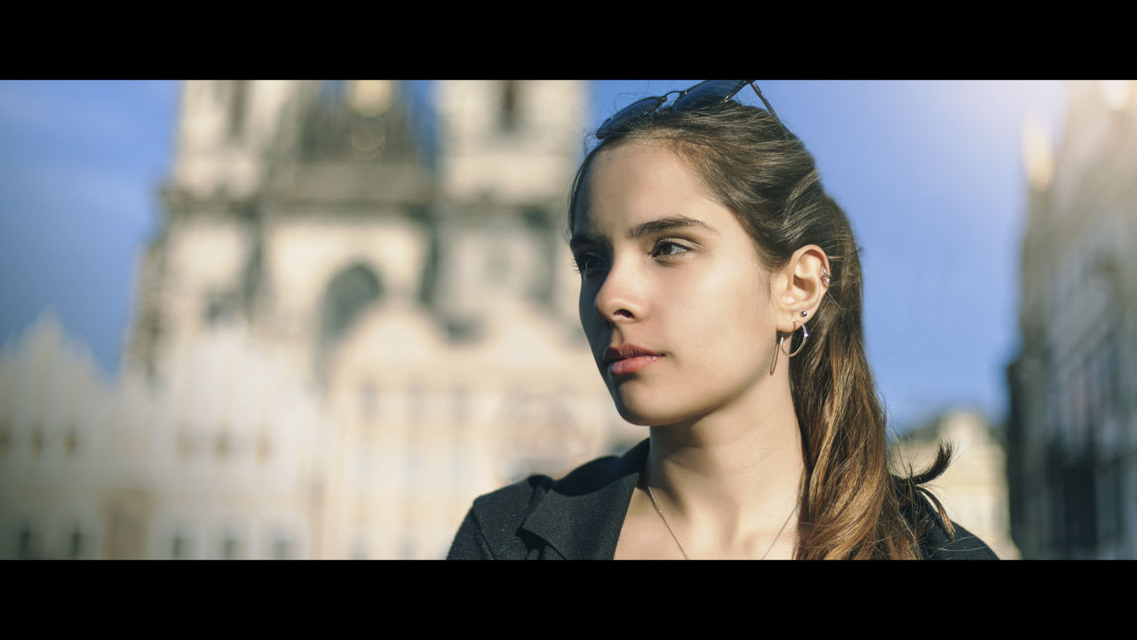 PORTRAIT OF YOUNG WOMAN LOOKING AT CITY IN BACKGROUND