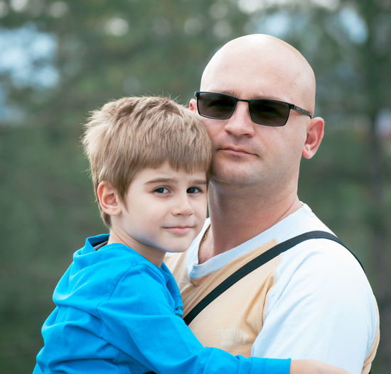 Caucasian father and son hugging outdoors Child Enjoyment Father & Son Hope Lifestyle Love Male Outdoors Photography Sunglasses
