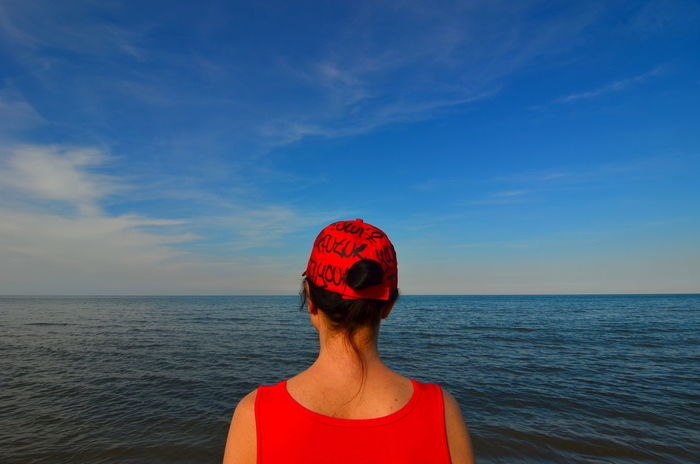 Alone Blue Brown Hair Candid Photography Colorfull Day Dreaming Feel The Journey Freedom From The Back Hat In Front Of The Sea Nature Ocean Outdoors Red Red Dress Sea Sky Standing Tranquil Scene Tranquility Vacations Water Woman