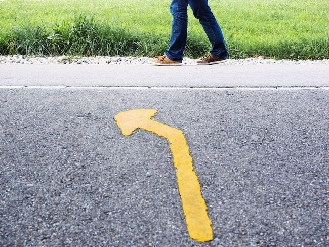 Yellow arrow sign on asphalt Legs And Feet Roadsign Turn Left Road Marking Low Section Asphalt Human Leg Transportation Road Road Sign Human Body Part Guidance One Person Communication Outdoors Yellow One Man Only