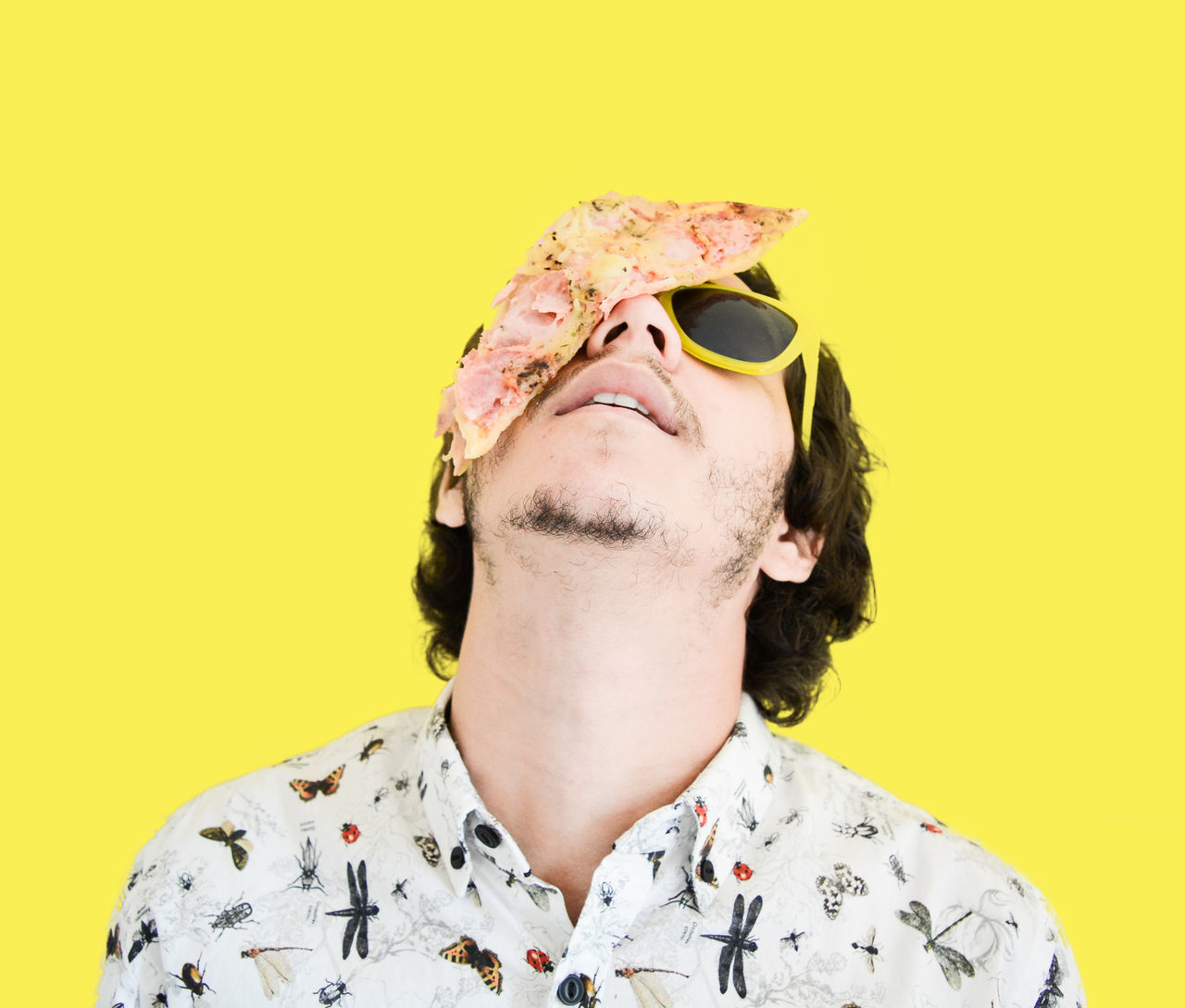 Close-up portrait of man with pizza on face